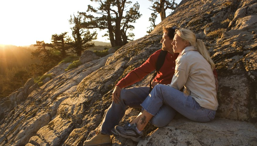 A couple watching the sunset on a weathered rock wall.