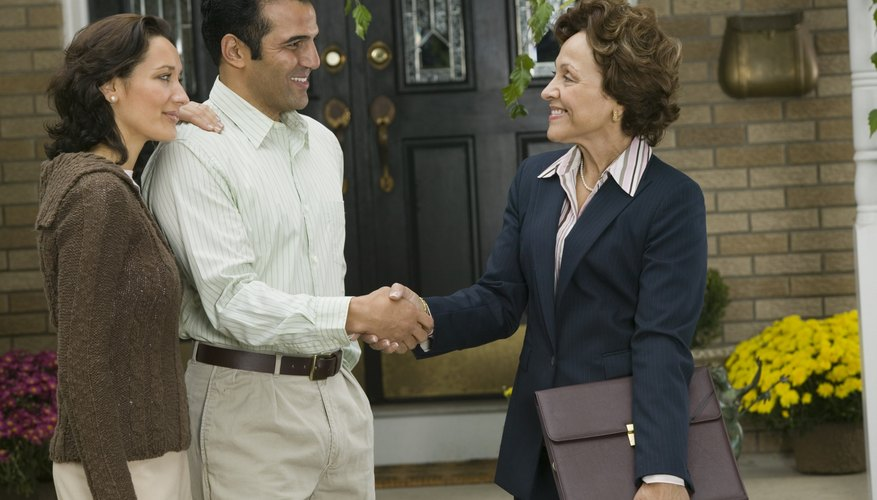 Couple shaking hands with real estate agent.