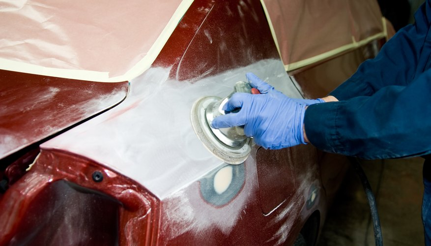 Mechanic polishing automobile in body shop