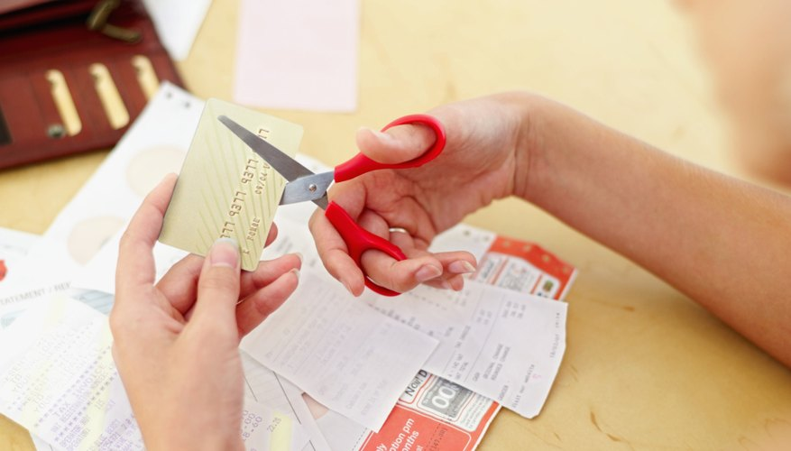 A woman is cutting up her credit card bills.