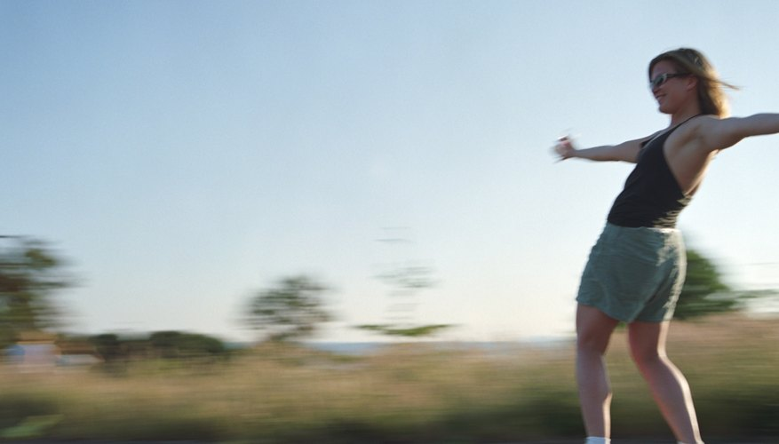 Young woman longboarding, side view (blurred motion)