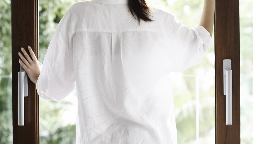 A woman stands at a patio door wearing a man's shirt.