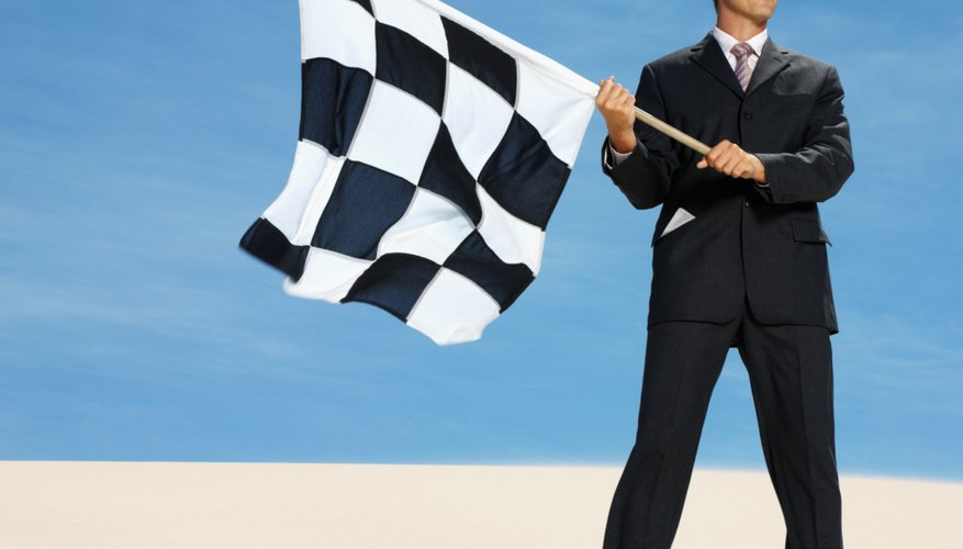 businessman in desert waving chequered flag, low angle view