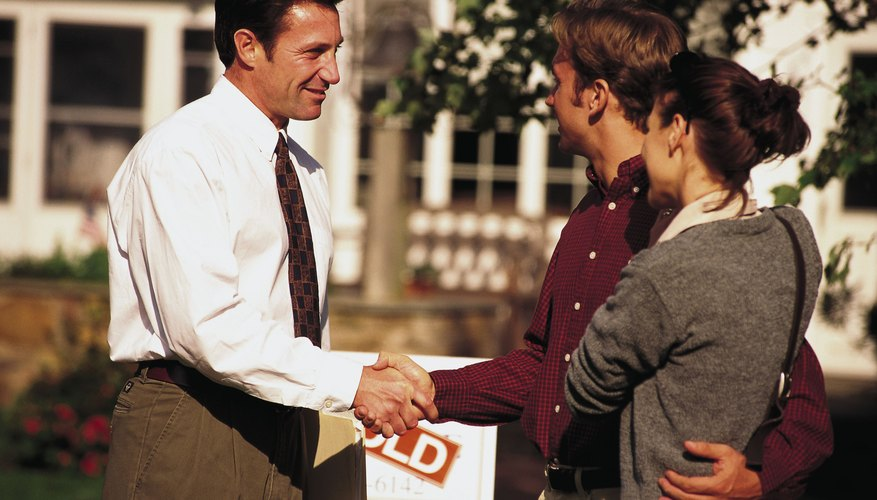 Couple shaking hands with businessman in front of house
