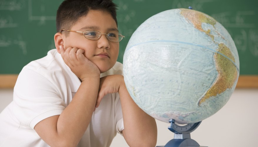 Young student looking at a globe.