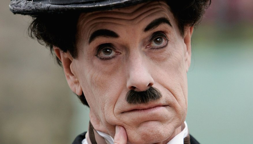 The actor impersonating Charlie Chaplin conveys thoughtfulness through pantomime.