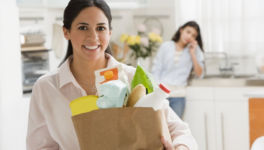 A woman is bringing her groceries into the house.