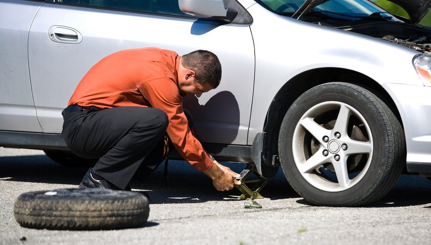 Man fixing flat tire on car