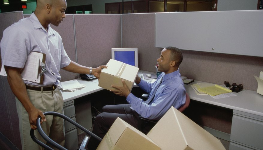 A delivery man handing a parcel to an office employee.