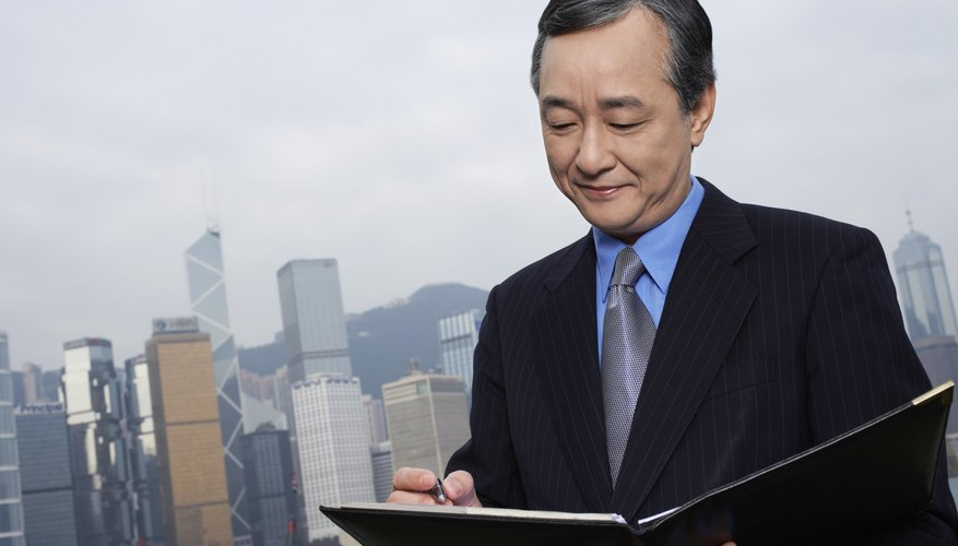 Middle-aged business man with documents, office building in background