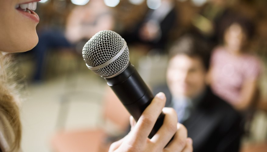 Woman speaking to audience on microphone