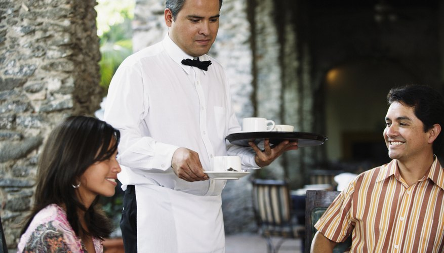 Waiter serving coffee to guests