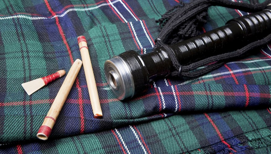 A bagpipe and three reeds laying on Scottish tartan.