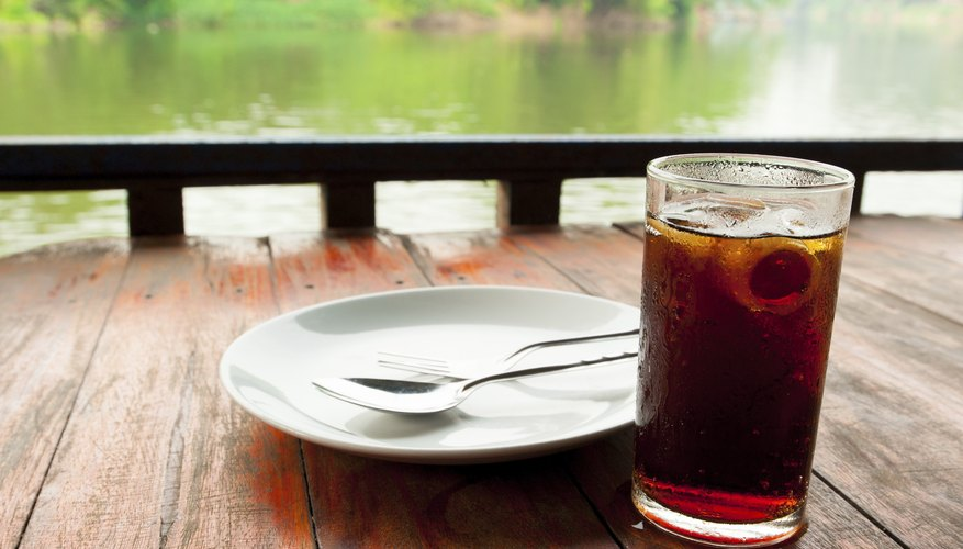 A glass of cola with ice on an outdoor table by a river.
