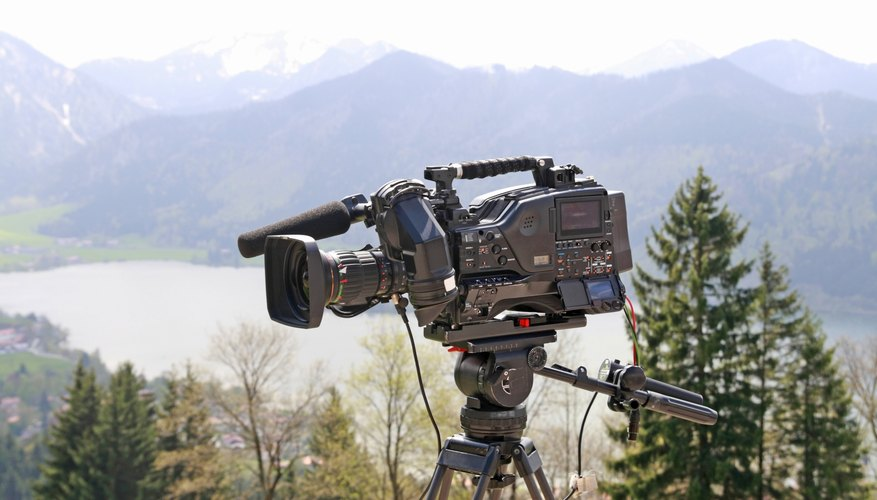 A movie camera is set up on a tripod in an outdoor setting.