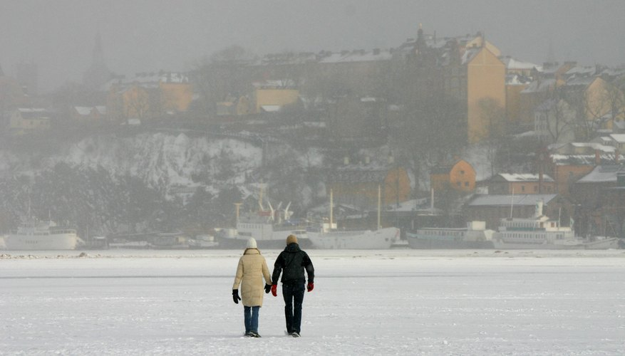 Couple walking on frozen water in Stockholm