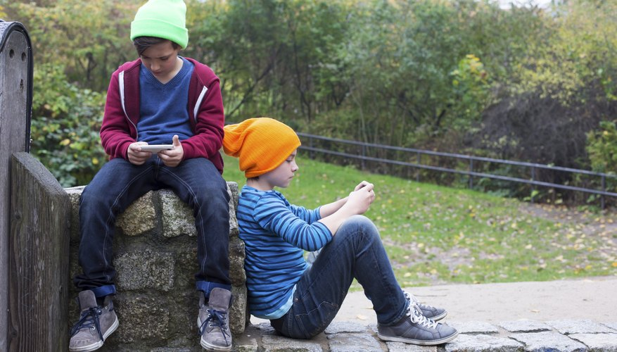 Two boys sitting on a stone wall using smart phones.