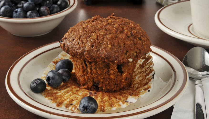 A healthy bran and flaxseed muffin with a couple of blueberries