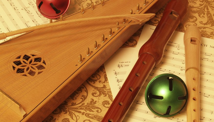 A bowed psaltery, recorder and bells on a rug with sheet music.