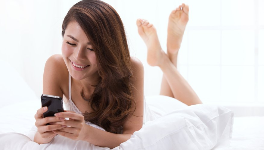 A young woman is looking at her cellphone.