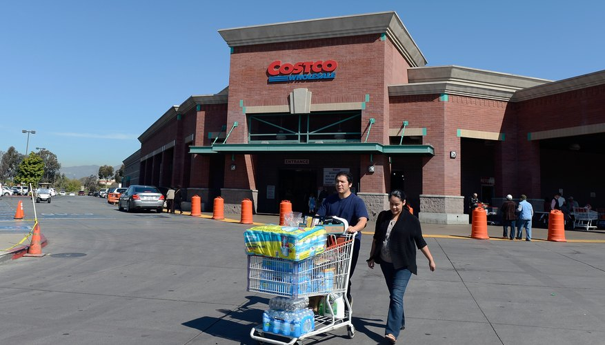 Consumers pushing a grocery cart of bulk items in the parking lot of a wholesale goods store.