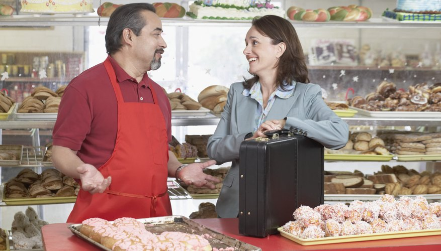 Male baker standing face to face with a businesswoman in a bakery