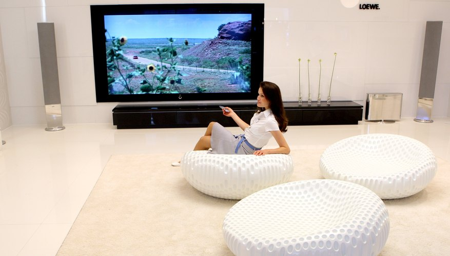 Woman with large LCD television and modern furnishings