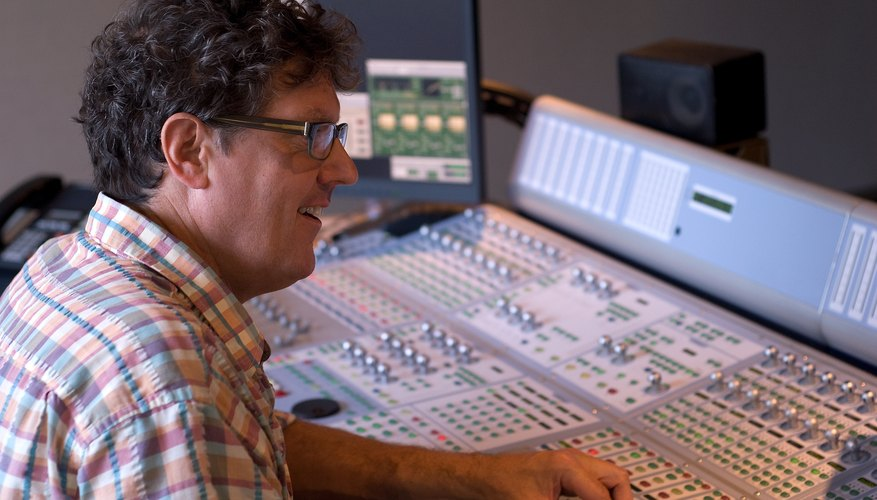 A sound engineer sits at the sound board.