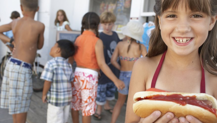 Girl (8-10) holding hotdog, smiling, portrait, children in background