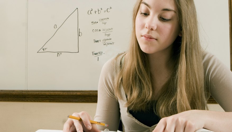 A student working with a calculator in a classroom.