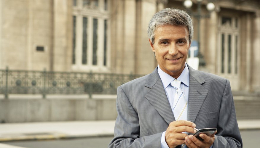 Mature businessman using palm pilot, smiling, portrait
