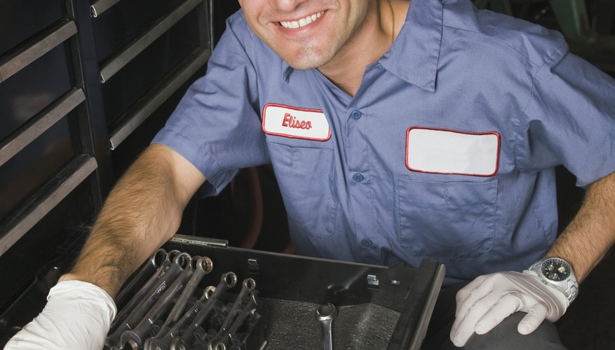 Smiling mechanic with wrenches