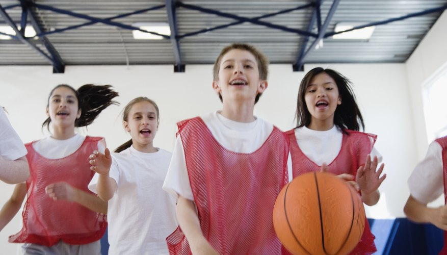 A group of preteens play basketball together.