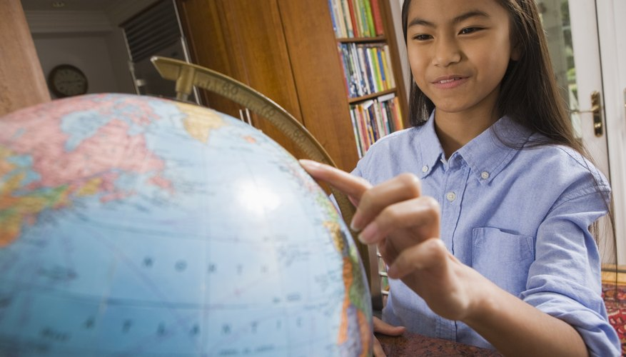 A girl pointing to a globe in the library.