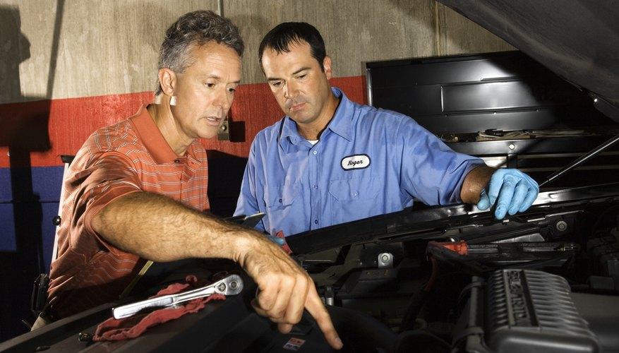 Auto mechanic and supervisor fixing vehicle