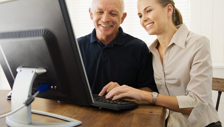 Woman helping man with computer