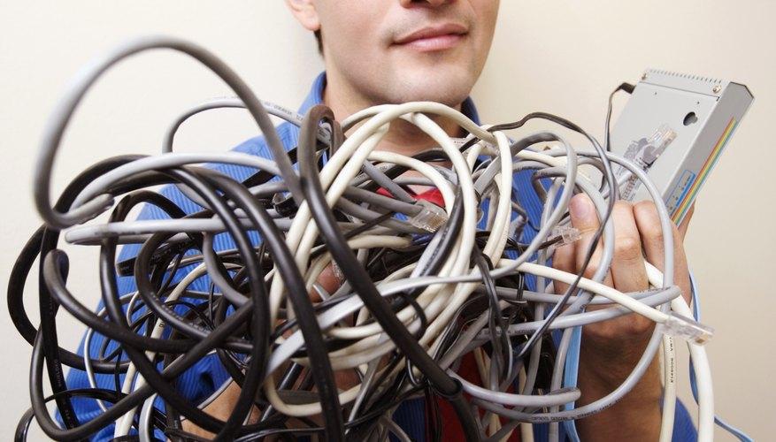 Businessman holding wires in server room, portrait