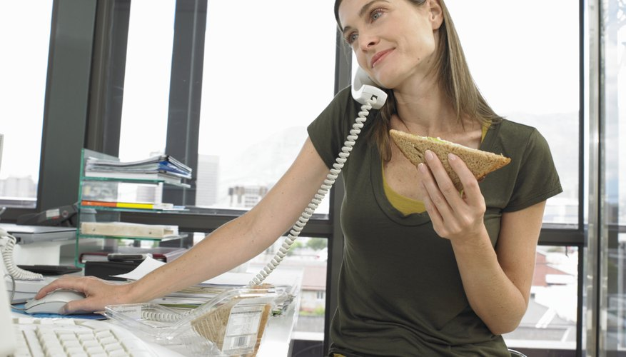 Woman sitting at desk using computer, on phone and holding sandwich