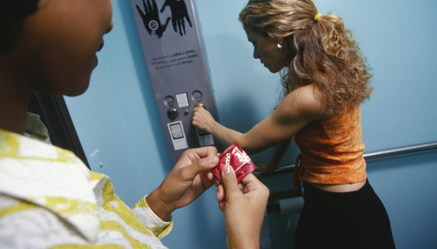 Young woman buying condoms from vending machine