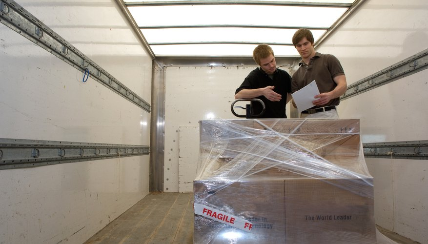 Two men with invoice and cargo on pallet inside truck