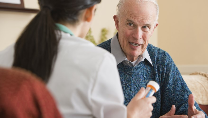 An elderly male patient talks to a nurse about medication