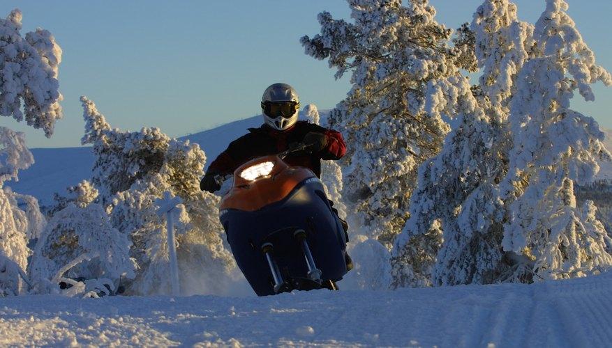Man driving snowmobile through forest