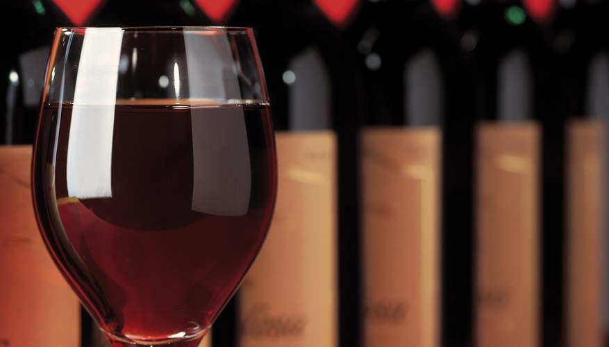 close-up of a glass of wine in front of an array of bottles