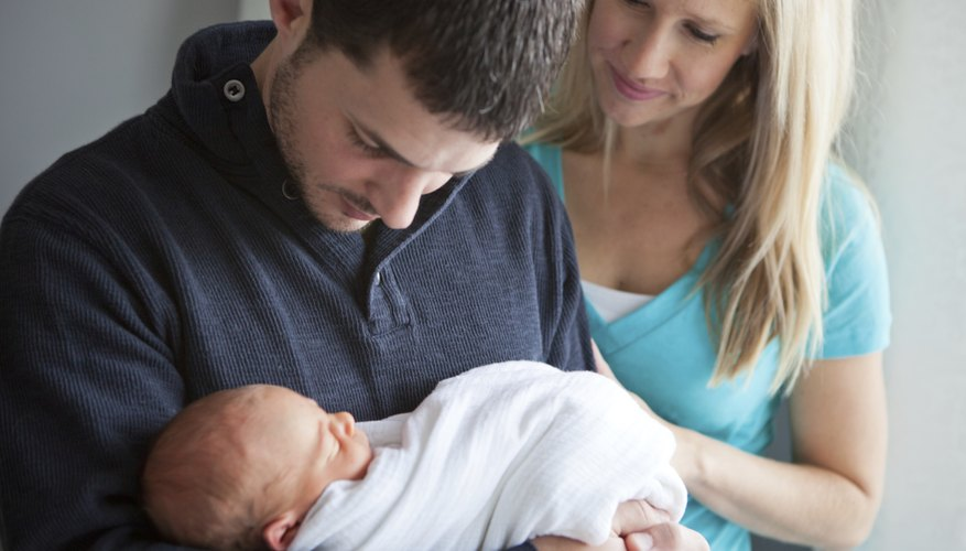 Couple holding their newborn baby.