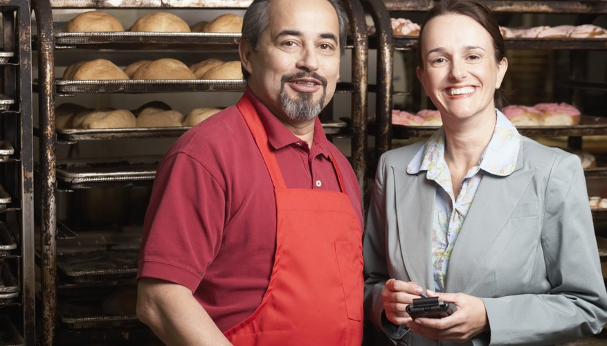 Portrait of a businesswoman smiling with a male baker in a bakery