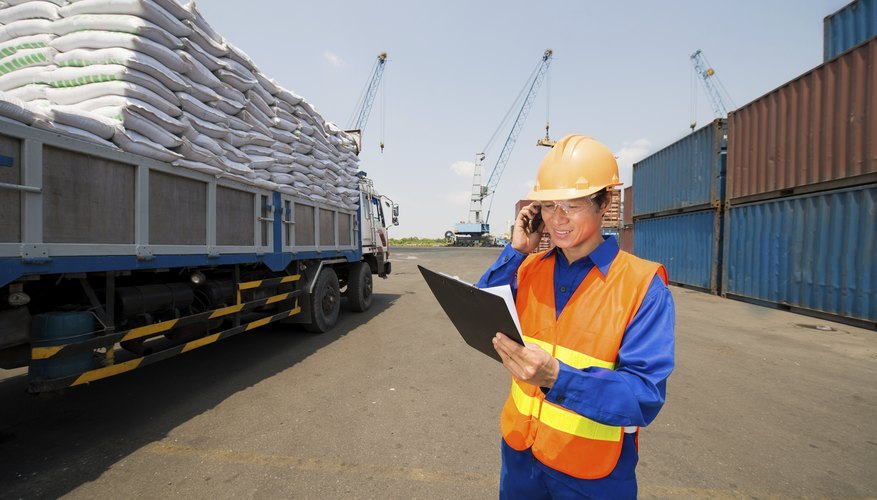 A shipping port worker checks inventory on a clipboard for cargo.