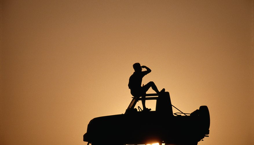 Man sitting on top of off road vehicle, silhouette
