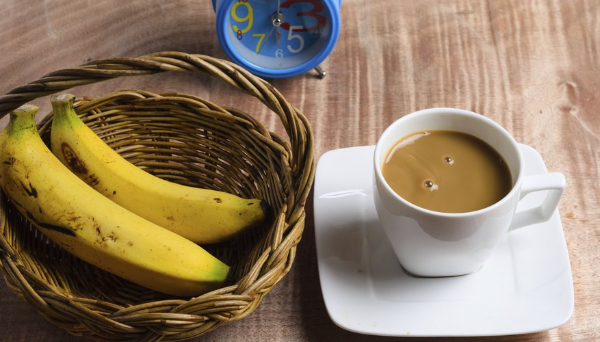 A cup of coffee and a basket of bananas.