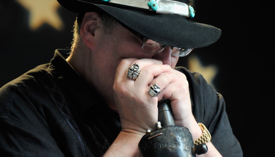 John Popper plays the harmonica while holding the microphone.
