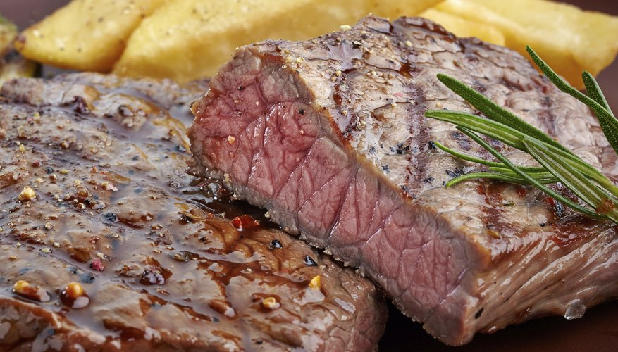 Grilled steak on a wooden cutting board.